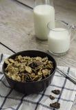 在碗和一杯的金黄和巧克力玉米片在木桌上的牛奶 图库摄影