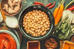 在碗和各种各样的健康烹调成份的鸡豆 素食主义者或素食主义者食物和吃 免版税库存图片