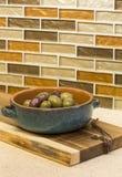 在碗和木切板的橄榄在与玻璃锦砖backsplash的设计的石工作台面在家庭厨房里 免版税库存图片