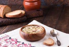 在碗和未加工的成份的冷的汤Okroshka在木桌上 免版税库存图片