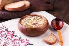 在碗和未加工的成份的冷的汤Okroshka在木桌上 库存照片
