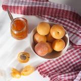 在碗和果酱的杏子在一张白色桌上的一个瓶子与一块红色和白色毛巾,手工制造夏天空白 库存图片