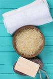 在碗和毛巾的海盐在蓝色木背景 免版税库存照片