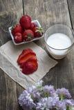 在碗和牛奶的新鲜的成熟草莓在木桌backgro 库存照片