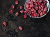 在碗和疏散莓果的冷冻野草莓 免版税图库摄影