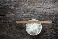 在碗和筷子的茉莉花米在木 免版税图库摄影
