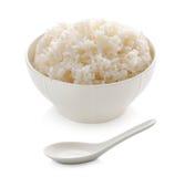 在碗和陶瓷匙子的米 库存照片