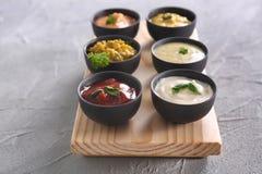 在碗的不同的鲜美调味汁在木板 库存图片