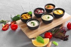 在碗的不同的鲜美调味汁在木板 免版税库存图片