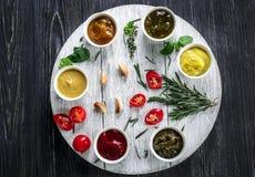 在碗的不同的鲜美调味汁在木桌上 免版税图库摄影
