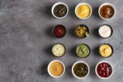 在碗的不同的鲜美调味汁在灰色桌上 免版税库存照片