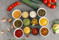 在碗的不同的鲜美调味汁在灰色桌上 库存图片