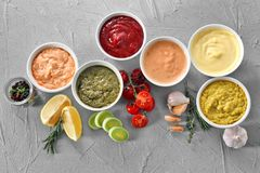 在碗的不同的鲜美调味汁在灰色背景 免版税库存图片