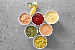 在碗的不同的鲜美调味汁在灰色背景 图库摄影