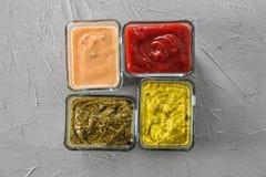 在碗的不同的鲜美调味汁在灰色背景 库存照片