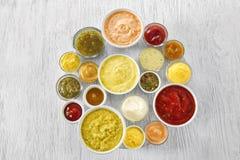 在碗的不同的鲜美调味汁在白色木桌上 免版税库存照片