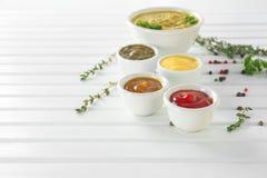在碗的不同的鲜美调味汁在白色木桌上 库存图片