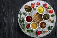 在碗的不同的鲜美调味汁用在木桌上的奶蛋烘饼 免版税库存照片