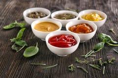 在碗的不同的鲜美调味汁用在木桌上的草本 库存图片