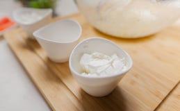 在碗的乳酪在厨房的切板 免版税图库摄影