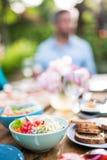 在碗的五颜六色的沙拉,朋友在庭院里会集分享一顿膳食 图库摄影