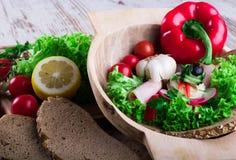 在碗的五颜六色的菜在书桌上用面包 库存照片