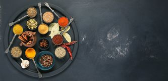 在碗的五颜六色,芳香香料在黑暗的背景 免版税库存照片