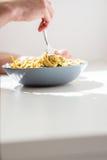 在碗的人旋转的意大利细面条面团使用叉子 免版税库存照片
