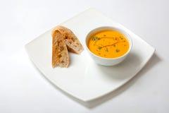 在碗的南瓜奶油色汤有面包片的 图库摄影