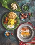 在碗的印地安食物饭食服务与香蕉叶子:咖喱,黄油鸡,米,扁豆, paneer, samosa, naan,酸辣调味品,香料 免版税库存图片