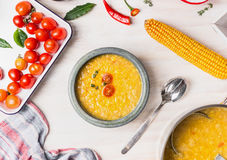 在碗的可口玉米汤有匙子和烹调成份的在白色木背景 免版税库存图片
