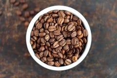 在碗的咖啡豆在棕色背景 免版税库存照片
