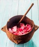 在碗的土气木匙子充满玫瑰花瓣 免版税图库摄影