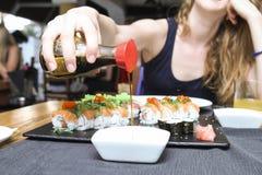 在碗的妇女倾吐的酱油 免版税库存图片