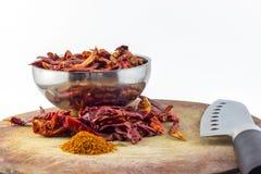 在碗的干辣椒 胡椒和刀子在木委员会,斩肉板 库存图片