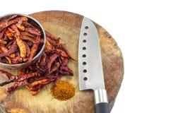 在碗的干辣椒 胡椒和刀子在木委员会,斩肉板 免版税库存图片