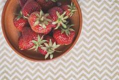 在碗的成熟红色草莓在Z形图案背景 免版税库存照片