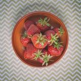 在碗的新鲜的成熟草莓在明亮的之字形背景 库存照片