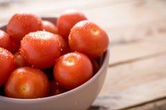 在碗的新鲜的西红柿在木背景 免版税库存照片
