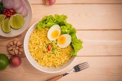 在碗的方便面有菜和煮沸的鸡蛋的在木头 库存图片