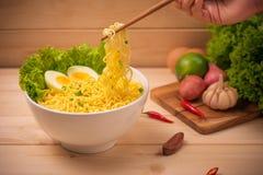 在碗的方便面有菜和煮沸的鸡蛋的在木头 库存照片