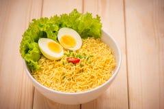 在碗的方便面有菜和煮沸的鸡蛋的在木头 免版税图库摄影