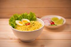 在碗的方便面有菜和煮沸的鸡蛋的在木头 图库摄影