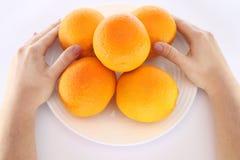 在碗的桔子用手 免版税库存照片