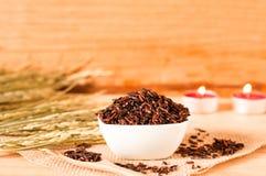 在碗的棕色未加工的米有木tabl的干粮食作物的 免版税库存照片