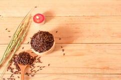 在碗的棕色未加工的米有木tabl的干粮食作物的 库存图片