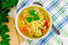 在碗的汤蔬菜通心粉汤在餐巾上面 免版税库存图片