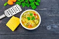 在碗的汤蔬菜通心粉汤在黑委员会上面 库存图片