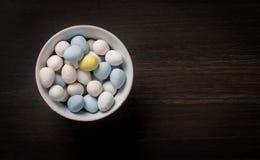 在碗的淡色复活节彩蛋在木背景 图库摄影