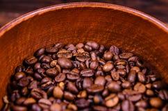 在碗的烤咖啡豆在木桌上 免版税库存图片